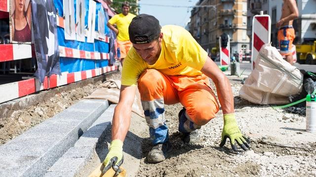 Ein Mann arbeitet bei über 30 Grad auf einer Baustelle in Zürich. (keystone)
