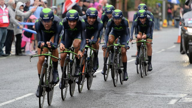 Die Fahrer des Movistar-Teams nehmen hintereinander fahrend eine Kurve in Angriff.