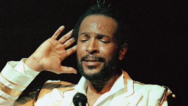 Ein bärtiger Schwarzer mit einem Mikrophon vor der Brust, die rechte Hand hält er offen ans Ohr.