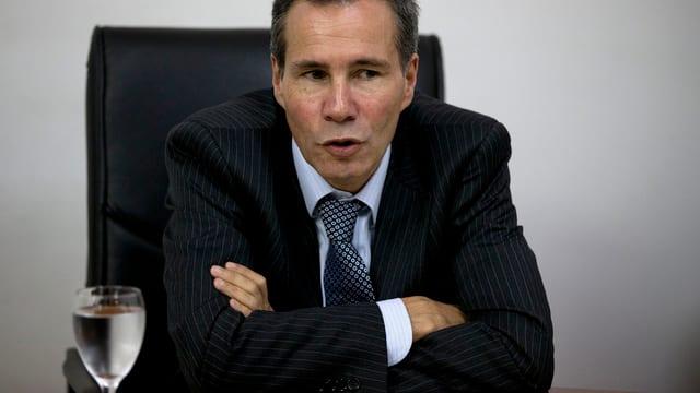 Nisman sitzt mit verschränkten Armen an einem Tisch