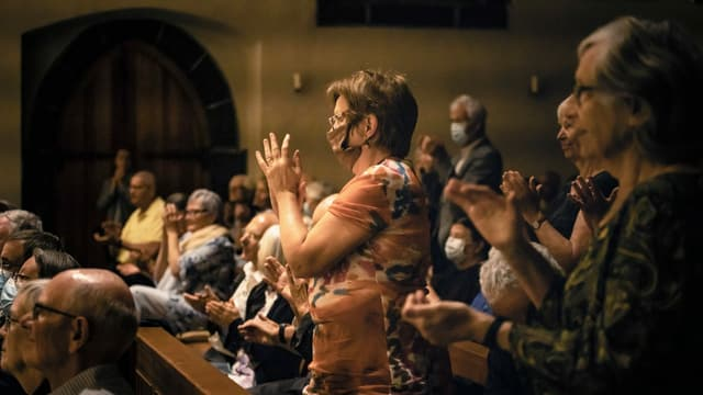 eine Publikum, das klatscht und eine Frau trägt eine Maske