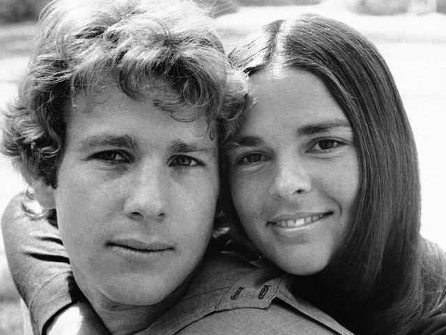 Schwarzweissbild: Eine junge Frau umarmt einen jungen MAnn.