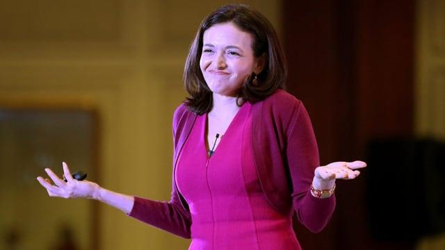 Sheryl Sandberg in pinkem Overteil und fragender Geste
