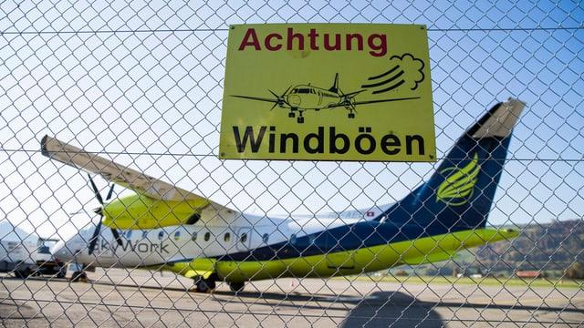 Schild «Achtung Windböen» am Flughafen Bern-Belp, im Hintergrund ein Skywork-Flugzeug