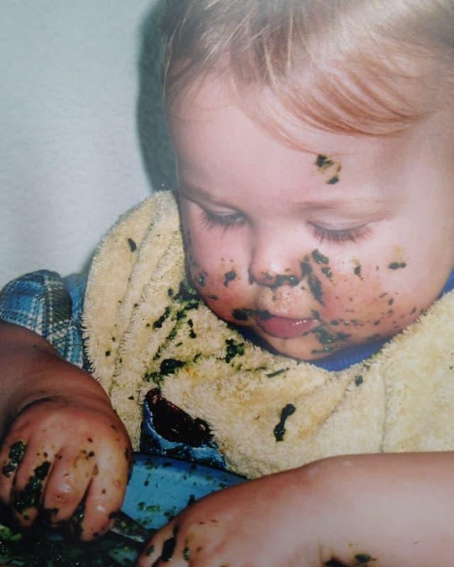 Ein Kind isst Spinat.