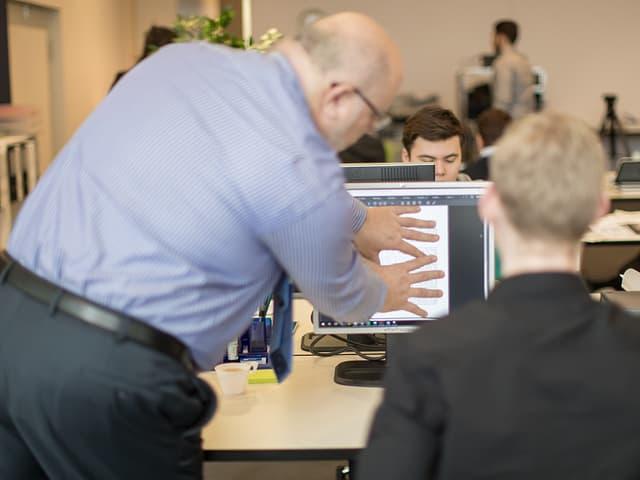 Ein Mann verdeckt mit seinen Händen einen Computerbildschirm.