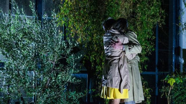 Ein umschlungenes Paar in einem nächtlichen Garten.