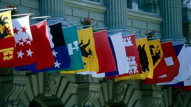 Flaggen versschiedener Kantone nebeneinander hängend.