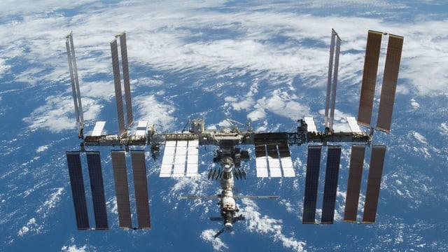 ISS, dahinter die Erde.