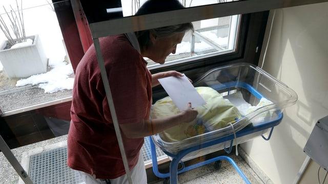 Frau steht bei einem leeren Babybett.