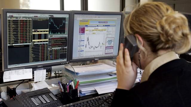 Bildschirm mit Börsenkursen und telefonierende Frau im Vordergrund