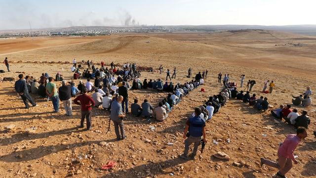 menschen sitzen mit dem Rücken zum Fotografen auf einem abschüssigen wüstenartigen Gelände, in der Ferne eine Stadt, darber Rauchschwaden.