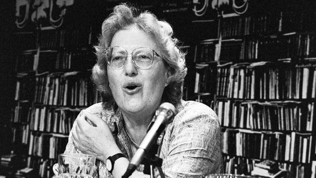 Schwarzweissfoto: Eine Frau vor einer Bücherwand spricht in ein Mikrofon.