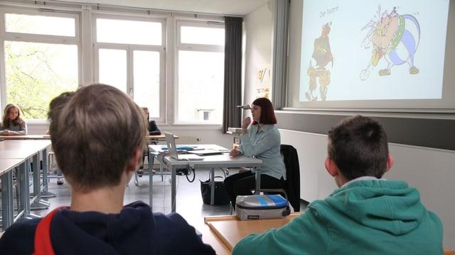 Blick in ein Schulzimmer, am Lehretisch unterrichtet eine Schülerin.