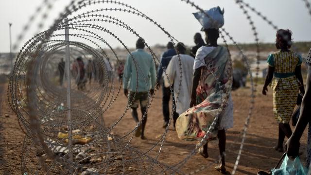 Menschen im Südsudan gehen auf einer staubigen Strasse neben einem Stacheldrahtzaun.