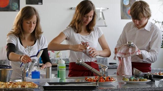 Drei Mittelschülerinnen bereiten gemeinsam eine Mahlzeit zu.