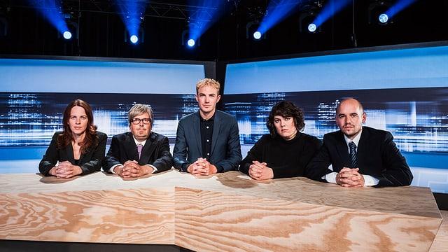 Michael Elsener sitzt mit dem Ensemble an einem massiven Holztisch im Studio. Alle fünf haben die Hände vor sich auf dem Tisch verschränkt.