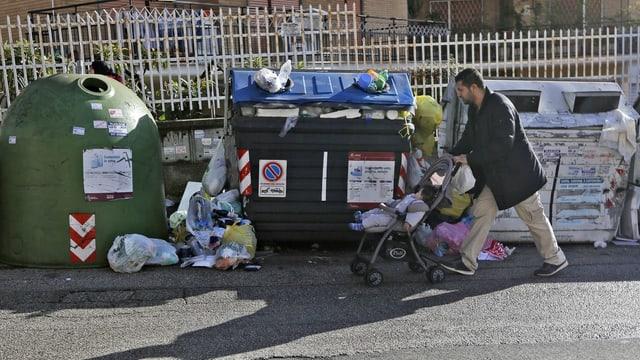 Mann mit Kinderwagen vor Abfallcontainern