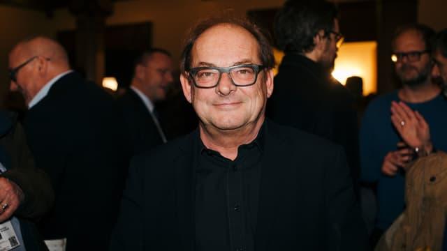 Ein Mann mit Brille, lachend.