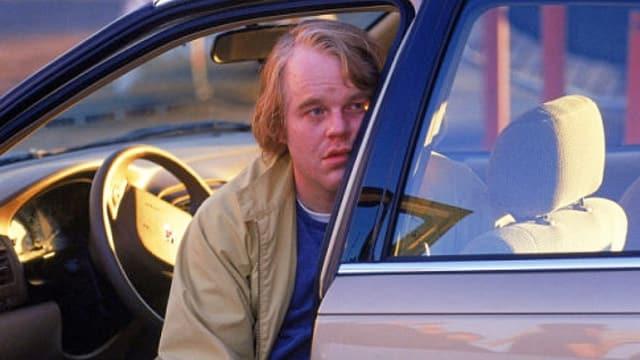 Seymour Hoffman schaut aus der Autotür eines Wagens.