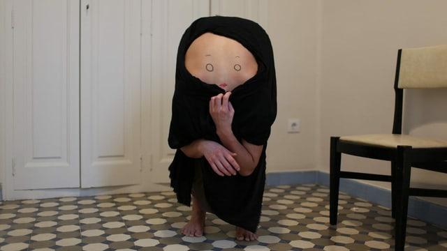 In einem Flur beugt sich ein Menschen vor, dessen Kopf man dadurch nicht sieht - stattdessen ist auf seinem Rücken ein Gesicht gemalt.