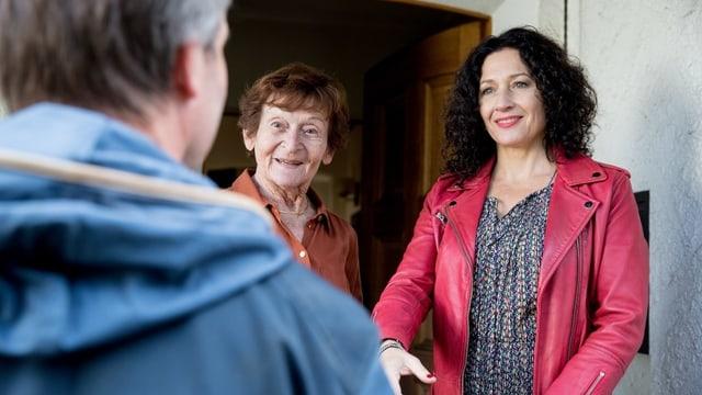 Links im Bild sieht man einen Mann von hinten. Vor ihm stehen eine ältere und eine jüngere Frau. Die ältere lächelt ihn an, die jüngere streckt ihm eine Hand entgegen.