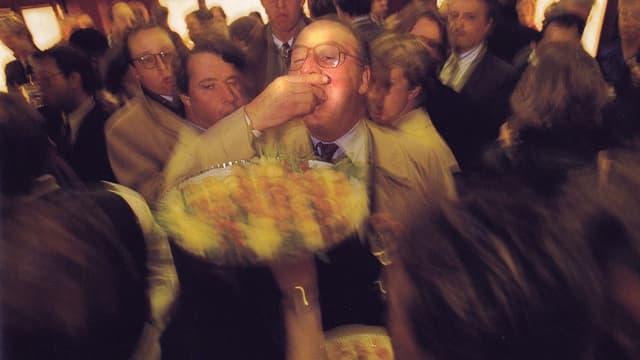 Mann in Festgesellschaft, stopft sich Häppchen in den Mund.