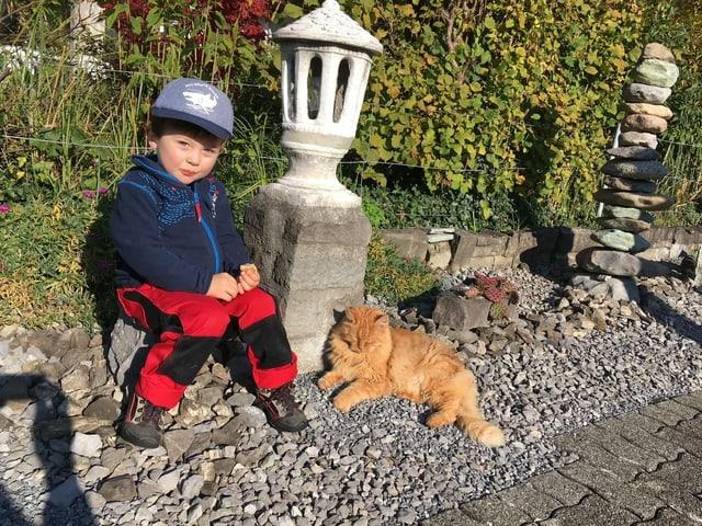 Ein kleiner Junge sitzt auf einer Mauer und eine Katze liegt auf dem Boden.