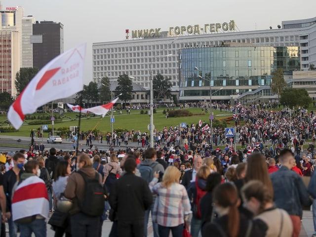 Tausende Demonstrierende schwenken Belarus-Fahnen und versammeln sich auf einem Platz.
