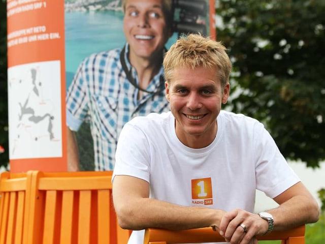 Porträt von Reto Scherrer auf dem orangen Wanderbänkli.