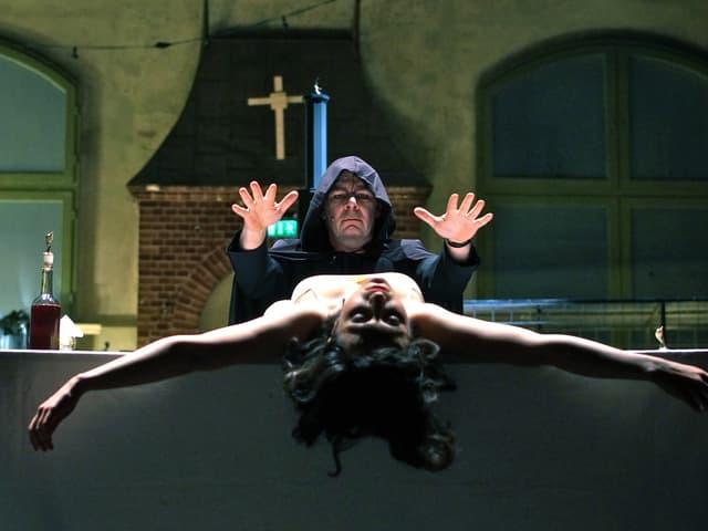 Bühnenszene: Okkultes Ritual mit Priester in schwarzer Kutte und einer Frau, die auf einem Tisch liegt.