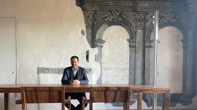 Er sitzt an einem Holztisch, dahinter eine weisse Wand, auf der in grau Rundbögen und Säulen gemalt sind.