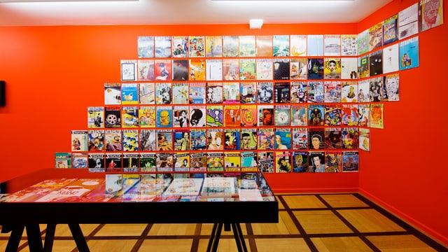 Totale eines Raumes dessen rote Wand mit Titelbildern von Strapazin-Ausgaben gepflastert ist.