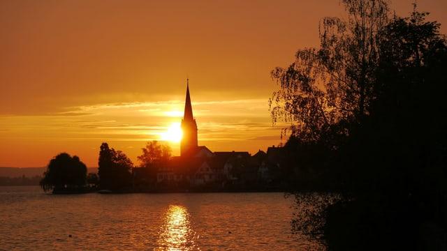 Die Sonne geht hinter der Kirche Berlingen auf.