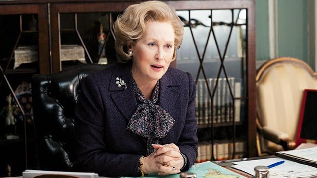 Frau (Margaret Thatcher) sitzt am Schreibtisch