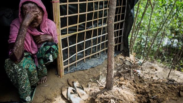 Eine Frau sitzt vor ihrer Hütte und verdeckt ihr Gesicht