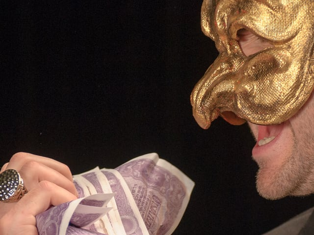 Mann mit goldener Maske und Geldscheinen in den Händen