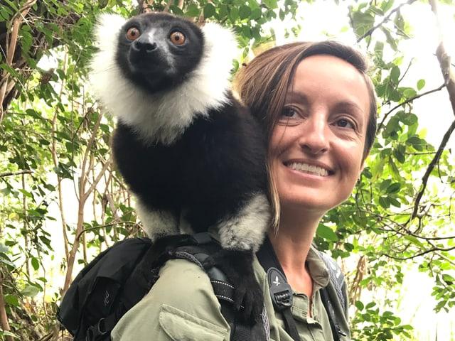 Forscherin mit einem weiss-schwarzen Halbaffen auf der Schulter