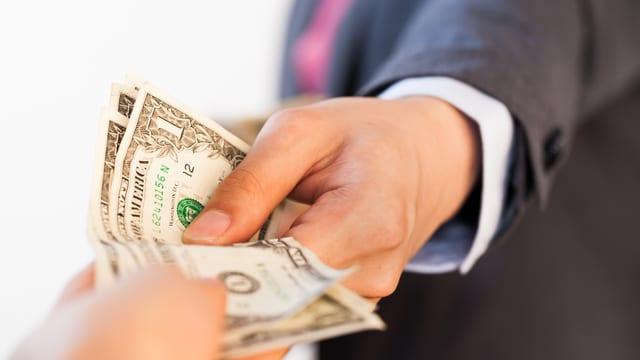 Zu sehen sind Hände, die Geld austauschen.