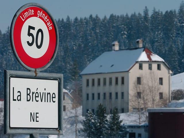 Ortsschild La Brévine, dahinter ein Gebäude, es liegt Schnee - auch auf den Bäumen und am Hausdach.