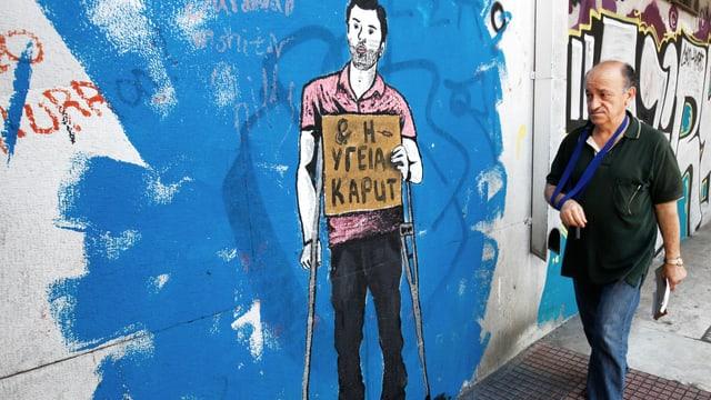 Ein Mann mit dem Arm in einer Schlaufe geht an einem Graffiti vorbei, die einen Mann mit Krücken zeigt.