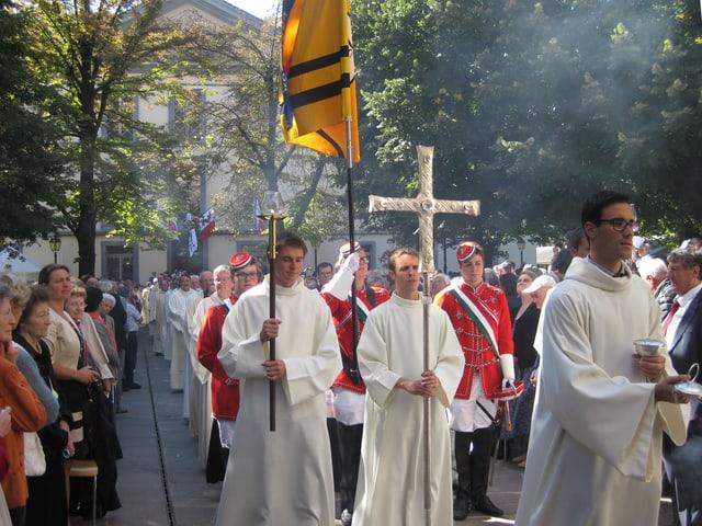 Priester mit Kreuzen und Fahne
