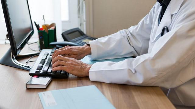Arzt am Computer, Akte liegt auf Tisch