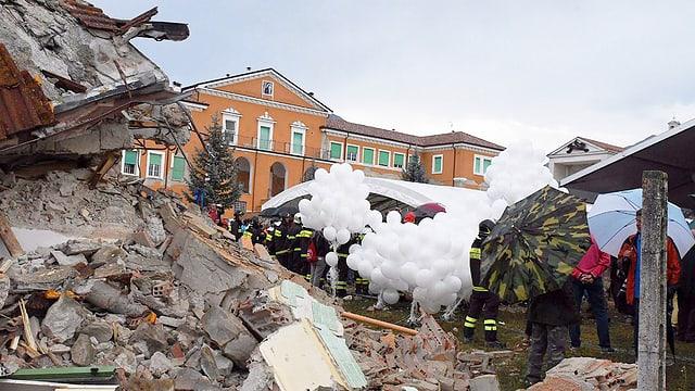Trauernde mit Ballonen neben Trümmern.