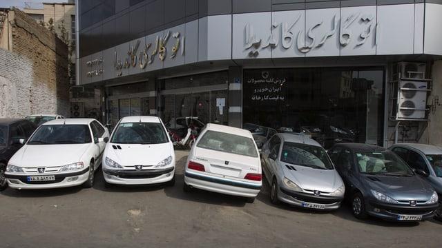 Vor einem iranischen Autogeschäft stehen verschiedene Peugeot-Modelle.
