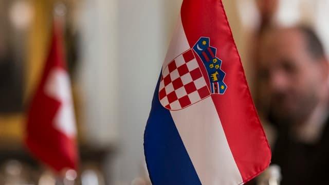 Ein Schweizer- und ein Kroatien-Fähnchen auf einem Tisch, im Hintergrund ein Mann.