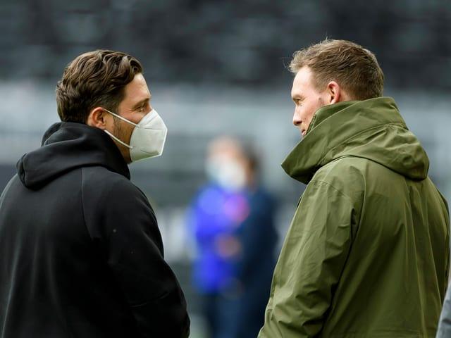Edin Terzic mit Mund-Nasenschutz (links) und Julian Nagelsmann (rechts) miteinander im Gespräch.