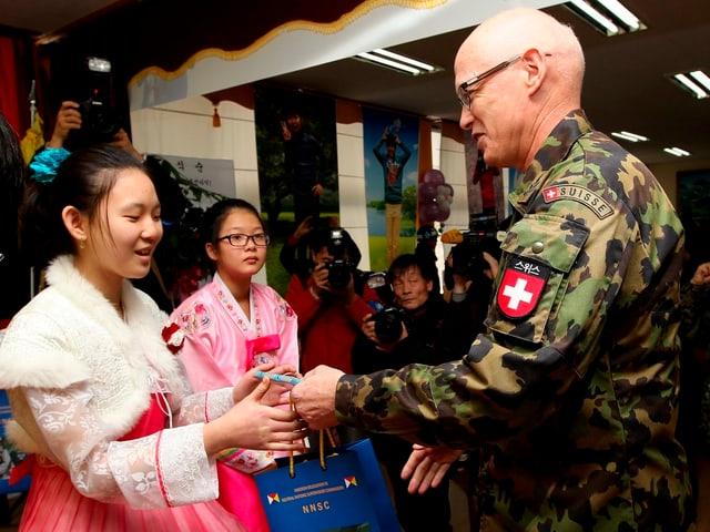 Ein Schweizer Soldat in Uniform wird von koreanischen Frauen begrüsst.