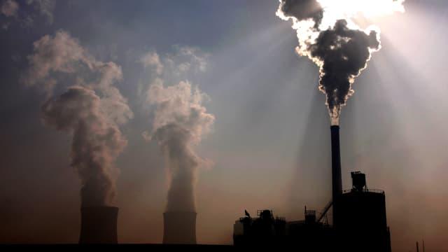 Kohlekraftwerk mit einer Rauchwolke, durch die die Sonne hindurchscheint. Daneben im Hintergrund: die Kühltürme von zwei Atomkraftwerken.