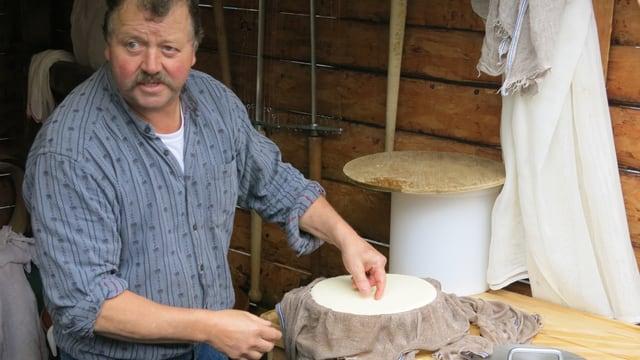 Mann bei der Käseherstellung.